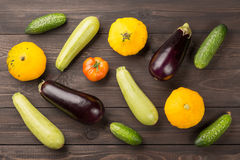 Vegetarian healthy food with vegetables. Tomato, cucumbers, bush pumpkins, eggplants nd marrows on dark wooden table. Stock Images