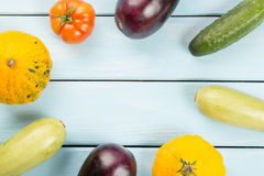 Vegetarian healthy food with vegetables. Tomato, cucumbers, bush pumpkins, eggplantsand marrows on blue wooden table with copy spa Stock Image