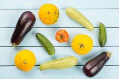 Vegetarian healthy food with vegetables. Tomato, cucumbers, bush pumpkins, eggplantsand marrows on blue wooden table. Royalty Free Stock Image