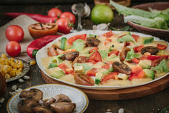 Vegetarian home made pizza with mushrooms and vegetables over wooden table, surrounded by ingredients.  Stock Photo