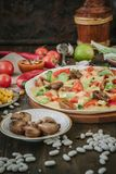 Vegetarian home made pizza with mushrooms and vegetables over wooden table, surrounded by ingredients.  Royalty Free Stock Photography