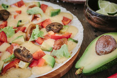 Vegetarian home made pizza with mushrooms and vegetables over wooden table, surrounded by ingredients.  Stock Photography