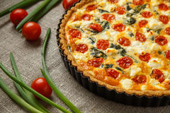 Vegetarian homemade pie, Quiche with tomatoes, spinach and feta cheese. Stock Photo