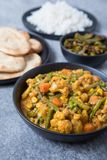 Vegetarian Indian Meal. Indian vegetable korma curry in a black bowl in the foreground with Indian side dishes in the background. White rice, naans and okra in a royalty free stock photo