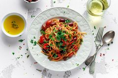 Vegetarian Italian Pasta Alla Puttanesca with garlic, olives, capers with on white plate. Vegetarian Italian Pasta Alla Puttanesca with garlic, olives, capers stock image