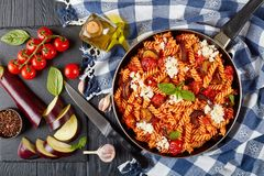 Vegetarian Italian Pasta fusilli alla Norma. With eggplant, tomatoes, basil, ricotta cheese in a skillet on a wooden table with ingredients at the background Royalty Free Stock Photo