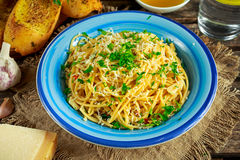 Vegetarian Italian Pasta Spaghetti Aglio E Olio with garlic bread, red chili flake, parsley, parmesan cheese and glas of Royalty Free Stock Photography