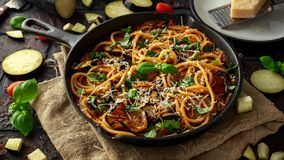 Vegetarian Italian Pasta Spaghetti alla Norma with eggplant, tomatoes, basil and parmesan cheese in rustic skillet pan. Vegetarian Italian Pasta Spaghetti alla stock images