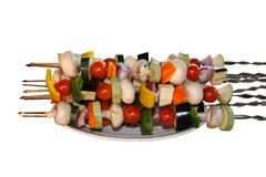 Vegetarian kebab. Vegetables and mushrooms on skewers are planted on a plate Royalty Free Stock Photo