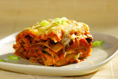 Vegetarian lasagna. A serving of vegetarian lasagna on a plate. Contain red beans with tomatoes, onions and cheese royalty free stock photo