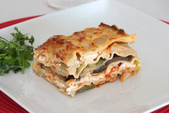 Vegetarian Lasagna. With eggplant, courgette, sweet potatos and tomato sauce on a white plate Royalty Free Stock Photo