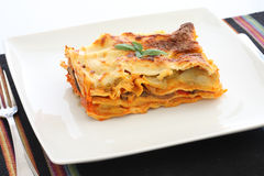Vegetarian Lasagna. With eggplant, courgette, sweet potatoes and tomato sauce on a white plate Royalty Free Stock Images