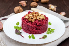 Vegetarian Lenten dish: a salad of beets with walnuts and garlic in a white plate Royalty Free Stock Photos