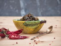 Vegetarian light salad with seaweed and sesame in a ceramic decorative salad bowl, shot from the side. In the foreground of a white table lies a bunch of red royalty free stock images