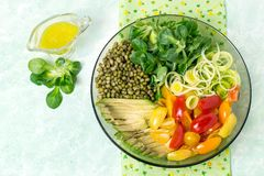 Vegetarian lunch bowl with beans mung and fresh vegetables. Vegetarian lunch bowl with beans mung, avocado, leek, cherry tomatoes, corn lettuce on light green Royalty Free Stock Photos