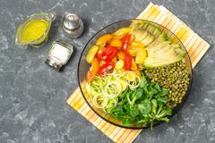 Vegetarian lunch bowl with beans mung and fresh vegetables. Vegetarian lunch bowl with beans mung, avocado, leek, cherry tomatoes, corn lettuce on gray Stock Image