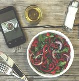 Vegetarian lunch. Salad of fresh vegetables, greens and red sweet peppers with olive oil. On the smartphone screen, a lunch displa stock photo