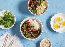 Vegetarian lunch table in the asian style - rice, noodles, vegetable stir fry, boiled eggs. On a blue background Stock Image