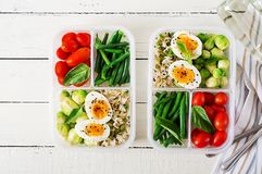 Vegetarian meal prep containers with eggs, brussel sprouts, green beans and tomato. Dinner in lunch box. Top view. Flat lay royalty free stock photography