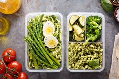 Vegetarian meal prep containers with pasta and vegetables. Vegetarian meal prep containers with eggs, zucchini noodles and pasta with green pesto sauce and royalty free stock photography