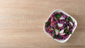 Vegetarian menu - salad of cabbage and radish in the bowl. On wooden background - top view Stock Photos