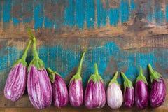 Vegetarian menu template - small fresh eggplants on wooden table Stock Photos
