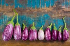 Vegetarian menu template - small fresh eggplants on wooden table Stock Photo
