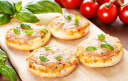 Vegetarian mini pizzas. Homemade vegetarian mini pizzas served on a wooden board Stock Images