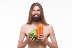 Vegetarian. Naked body vegetarian smiling for photo camera. Man carrying cabbage and carrots isolated on white background Royalty Free Stock Photography