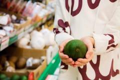 Vegetarian och nya frukt och grönsaker på naturen av temat: mänsklig hand som rymmer en avokado arkivbilder