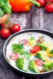 Vegetarian omelette with broccoli cherry tomato orange pepper an Stock Photo