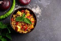 Vegetarian paneer biryani at black background. Paneer biryani is traditional veg indian cuisine dish with paneer cheese, basmati rice, masala, chili pepper stock images