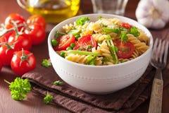 Vegetarian pasta fusilli with tomato peas herbs Stock Images