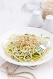 vegetarian pasta with zucchini and nuts on white table, vertical Stock Photography
