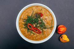 White bowl of a healthy vegetarian pea soup with pumpkin seeds, chives and spicy chilli. Orange color, black background stock photos