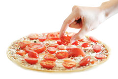 Vegetarian pizza. A hand putting fresh tomatoes on a vegetarian pizza Royalty Free Stock Photography