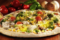 Vegetarian pizza. Close up of vegetarian pizza with tomatoes in background Royalty Free Stock Photography