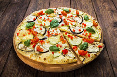 Vegetarian pizza with aubergines and zucchini. Delicious italian vegetarian pizza, with cherry tomatoes, peppers, aubergines and zucchini - thin pastry crust at Stock Photos