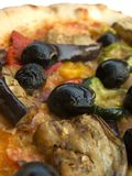 Vegetarian pizza closeup. Macro shot of Italian mozzarella cheese and tomato pizza hot from the oven with mixed vegetable topping of olives, eggplant, zucchini Royalty Free Stock Image
