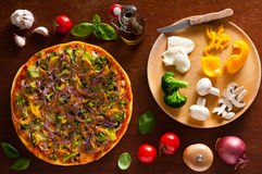 Vegetarian pizza and ingredients. Traditional vegetarian pizza and vegetable ingredients Stock Images