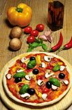 Vegetarian pizza and ingredients. Vegetarian pizza and some ingredients in the background Stock Images