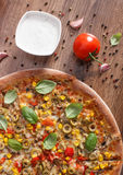 Vegetarian pizza and ingredients with spices on rustic wooden background, fast food Royalty Free Stock Photos