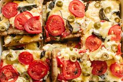 Vegetarian pizza made from mozzarella cheese, tomatoes and olives royalty free stock images