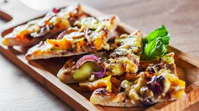 Vegetarian pizza with Mozzarella cheese, grilled zucchini, mushrooms, red onion, pepper and fresh basil. Italian pizza on wooden t. Able background stock image