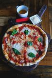 Vegetarian pizza with mozzarella cheese, tomatoes, spices and fresh Basil. Delicious Italian pizza. Sliced pizza Margarita on a stock photography