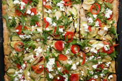 Vegetarian Pizza. In a pan, with mozzarella, onion, garlic, zucchini, cherry tomato, cottage cheese and salad rocket. Top view Royalty Free Stock Photos
