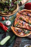 Vegetarian pizza party. Homemade pizzas with tomatoes, pesto, leafy greens and raw vegetables on shabby wooden background royalty free stock photography
