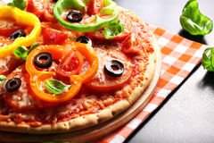 Vegetarian pizza with peppers, tomatoes, olives and basil. Hot, delicious, juicy, fresh-cooked pizza Royalty Free Stock Images