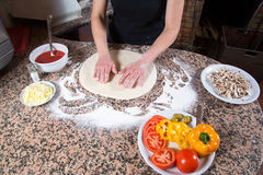 Vegetarian Pizza Preparation - Baker Kneading Dough Surrounded By Ingredients On Marble Table In The Kitchen Stock Photo