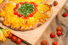 Vegetarian pizza. With pumpkin flowers, tomatoes and peas Royalty Free Stock Photo
